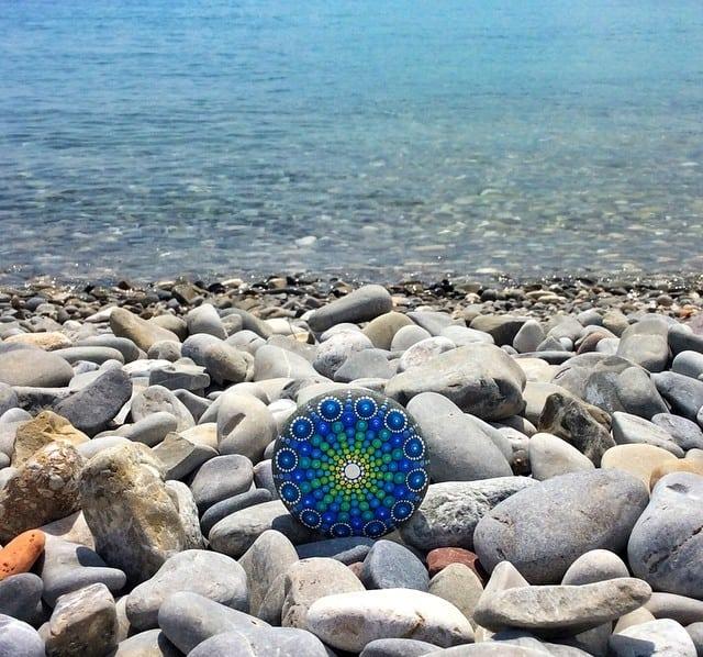 Девушка собирает камни на пляже и делает из них настоящие произведения искусства